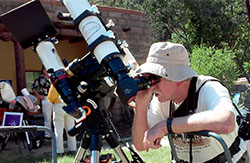 adult looking through a telescope